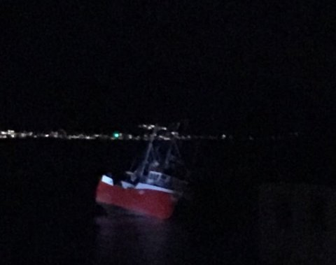 """PÅ GRUNN: Sjarken ligger """"på halv åtte"""" i fjæra i Nordvågen. Foto: Nordlys-tipser"""