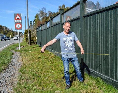STØYSKJERM:  Det er mer enn nok av plass til fortau på utsiden av støyskjermen i Hegnaveien, mener Tron Davidsen. Han og naboene er imot at  kommunen skal kappe hagene deres.