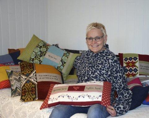 TRENGTE EN GAVE: Anne Karen Hagen Kjølhamar startet med å sy ei pute til ei venninne. Nå har hun senga full av unike puter med forskjellige tekster. – Jeg får en egen ro over meg når jeg syr. Det er så gøy, smiler hun.