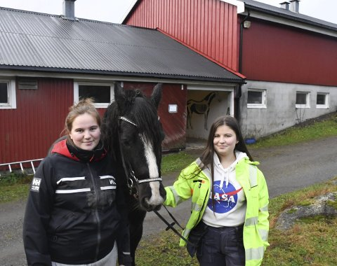 Trives: Emma Schanke Kleivane (t.v) og Tuva Danielsen er glad i hester og andre dyr. De forteller at de og andre elever i 1. klasse naturbruk er ganske sjokkert over forslaget om å fjerne både hest- og dyrefag og agronomklassen på Tvedestrand vgs.