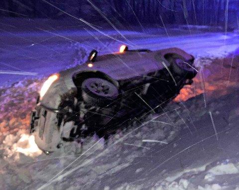 OPPDAGET AV EN BRØYTEBIL: I et voldsomt snøvær har bilen havnet utenfor veien, den ligger på siden en tre fire høydemeter ned i skråningen.