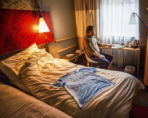 Lyseblått klenodium: Jan Tore Stenersen på hotellrommet i Manchester. Drakten på senga er signert av fotballstjerner som, Yaya Touré, David Silva og Joe Hart.foto: stig sandmo