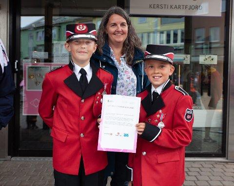 Pengegave: Valnesfjord skolekorps ble tildelt 20.000 kroner. Hovedsakelig til å kjøpe nye uniformer til neste års jubileumsfeiring. Her står to representanter fra bygdas skolekorps, med det synlige beviset på at pengegaven ble deres.