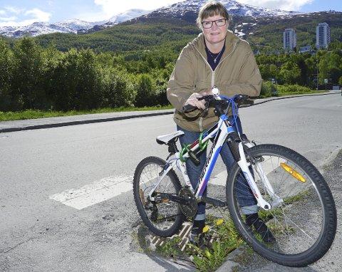PÅ TO HJUL: Marit R. Birkeli vil at den store skogen bak henne skal gi plass for parkeringsplasser for opp mot hundre biler. De kjørende skal kunne finne seg elsykler eller vanlige sykler der, og rulle inn i byen på to hjul. Foto. Fritz Hansen