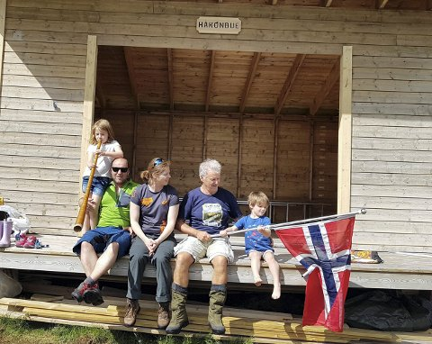 HÅKONBUE: Bildet er fra åpningen av gapahuken i fjor. Olav Høva Næss sitter med flagget i hånden og datteren med familie rundt seg.