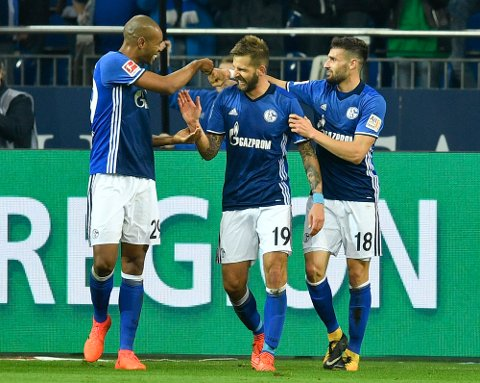 Schalke's Guido Burgstaller, center, is congratulated by teammates Naldo, left, and Daniel Caligiuri, right, after scoring his side's second goal challenge for the ball during the German Bundesliga soccer match between FC Schalke 04 and FSV Mainz 05 at the Arena in Gelsenkirchen, Germany, Friday, Oct. 20, 2017. (AP Photo/Martin Meissner)