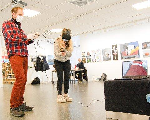 """NÅ ER JEG PÅ SOVEROMMET: Hedda Larsson fra Sofiemyr tester ut VR-brillene, som gir henne tilgang til Roald Amundsens hjem. - Nå er jeg på soverommet hans, utbryter hun. Noe vi som er """"utenfor"""" også kan se på skjermen. Her får hun teknisk hjelp av Anders Bache, som er fagkonsulent på Roald Amundsens hjem."""