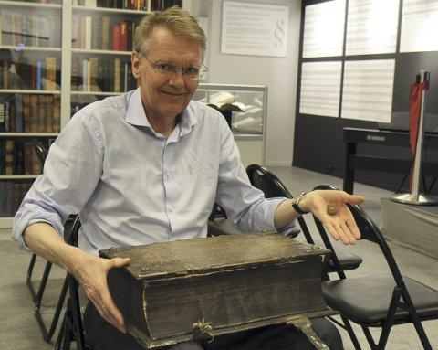 Liten og stor: Rune Arnhoff med to av museets omkring 3.000 forskjellige utgaver av Bibelen. Her viser han fram den største og minste i samlingen, som veier bare noen få gram.   Selv har han samlet på bibler i 30 år. alle FOTO: KJELL AASUM
