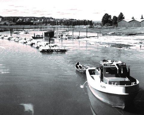UNIKT FOTO: Rauma i aksjon i 1959, det eneste kjente gamle bildet som viser tømmerslep i Nitelva ved Lillestrøm. Masta er lagt ned for at båten skal komme under brua.