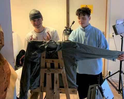 REDESIGNERE: Andreas Evensen Jørgensen (21) og Mons Jensen Grimstad (22) fra Storsand har startet opp sitt eget klesmerke, Eminus, som fokuserer på redesign, bærekraft og unikhet. Her er Mons (t.v.) avbildet i guttas atelier på Storsand, sammen med en av modellene deres.