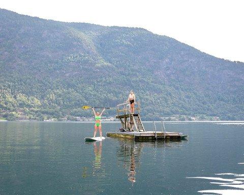 NYT SOLA: I Sogndal er Marusia (22), Ingvild (21) og Miriam (21) på padlebrett på fjorden. - Me må nyta sola, seier Marusia. (Foto: Natalie Liabø Hermansen)