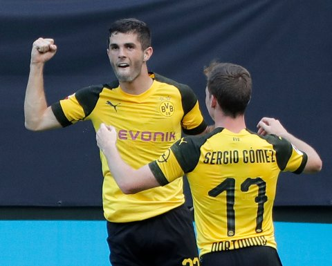 Borussia Dortmund's Christian Pulisic, left, celebrates with Sergio Gomez (17) after scoring a goal against Liverpool during the second half of an International Champions Cup tournament soccer match in Charlotte, N.C., Sunday, July 22, 2018. (AP Photo/Chuck Burton)