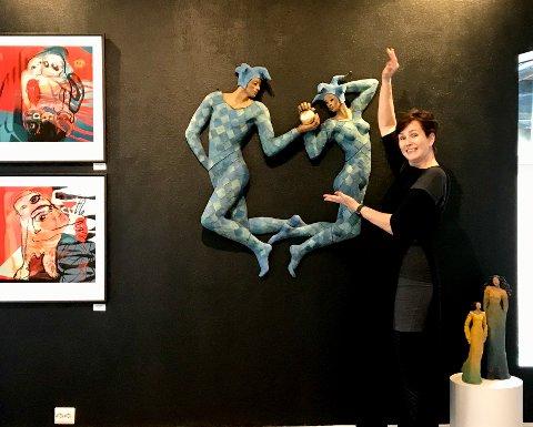 SKULPTUR: Ingun Dahlin med en av skulpturene hun har med til Fenka i år. Skulpturen bak heter gaven og skal symbolisere gullballen, en gave som symboliserer den store kjærligheten. Her fra lørdagens utstillingsåpning på Fenka.