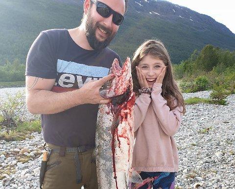 LITEN STORFISKER: Nora Alice Skorpen trodde nesten ikke sine egne øyne da den store fisken ble dradd opp på land. Hun måtte få litt hjelp fra pappa Daniel for å berge fisken