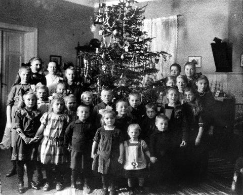 NØYSOM JUL: Det er julaften 1917, og noen barnehjemsbarn i Larvik er samlet til høytidelig fotografering rundt et andektig pyntet juletre. Barna hadde gjennom hele høsten spart penger til bittesmå gaver til hverandre. En av dem har fortalt at hun fikk nok til en hel kokesjokolade. Den delte hun opp i ruter og pakket inn i pent papir, skrev til og fra utenpå og la dem forventningsfull under treet. Rørende historie fra en tid før overfloden og sløseriet tok oss. Fram til 1925 holdt Larvik Barnehjem til det der hvor Larvik Rutebilsentral lå hele resten av 1900-tallet. Barnehjemmet på sin side levde videre i Eiriks gate til noen år etter krigen. Fra Per Nyhus:  larvikhistorier.no.