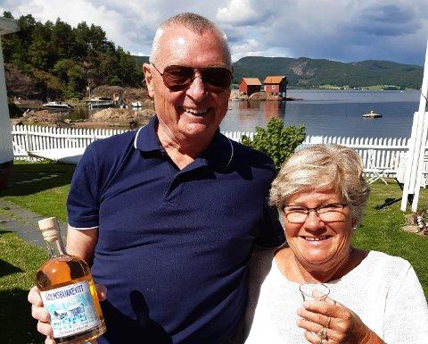 SMAK AV HOLMSBU: Finn Pettersen og Anne-Karine Grøtterud viser stolt fram smaken av Holmsbu på flaske med Bakkeskjær som symbol. - Motivet på etiketten er laget av Ragnar Haug, og også han var fornøyd med hvordan det ble, sier de.