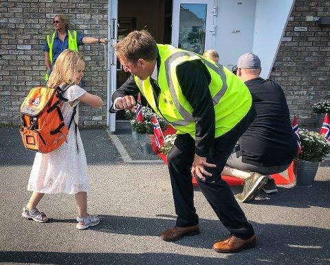 FØRSTE SKOLEDAG: Annabelle Mikkelsen (5) gjør koronahilsen med rektor ved Sandesundsveien barneskole Knut Raknerud Olsen.