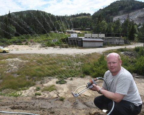 Vannspreder: Magne Ingolf Madsen i Vegårshei skytterlag har sørget for å vanne fangvollen på skytebanen ved hjelp av ei pumpe og vann fra elva. Foto: Øystein K. Darbo