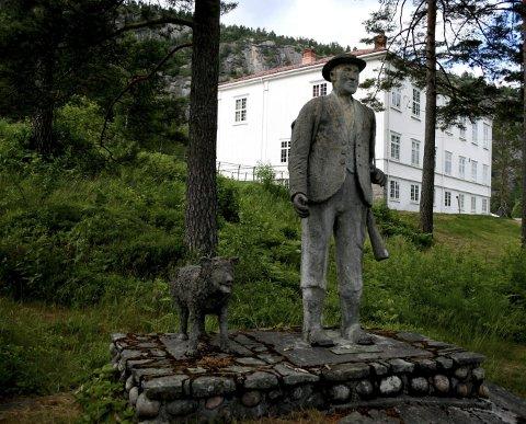 Vakkert, men utilgjengelig: Olav Seldal er sønn av Olav Tverstøyls nevø. Familien ønsker  at statuen av bjørnejegeren skal flyttes til et mer sentralt sted i Åmli. Kommunen har mottatt forespøreslen, som nå skal få en formell behandling. Foto: Åmli kommune
