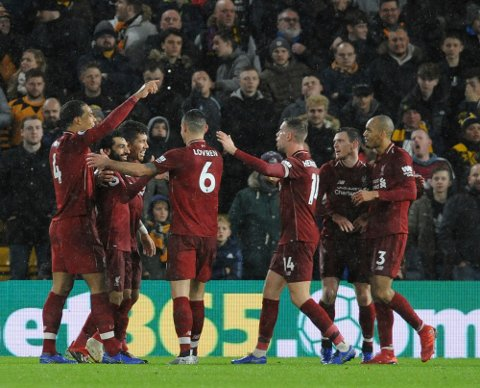 Liverpool's Mohamed Salah, second left, celebrates with his teammates after scoring his side's opening goal during the English Premier League soccer match between Wolverhampton Wanderers and Liverpool at the Molineux Stadium in Wolverhampton, England, Friday, Dec. 21, 2018. (AP Photo/Rui Vieira)