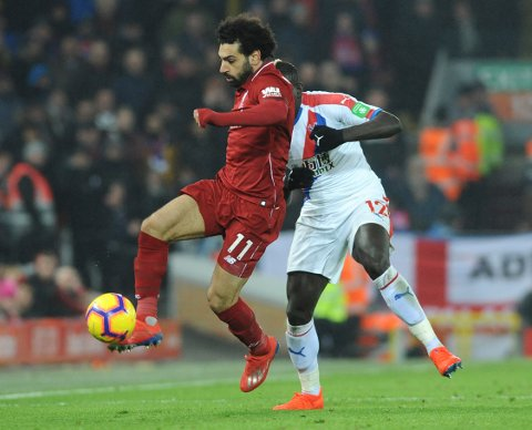 Liverpool's Mohamed Salah, left, and Crystal Palace's Mamadou Sakho challenge for the ball during the English Premier League soccer match between Liverpool and Crystal Palace at Anfield in Liverpool, England, Saturday, Jan. 19, 2019. (AP Photo/Rui Vieira)
