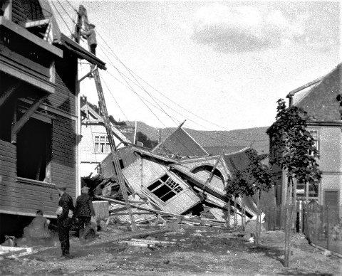 """""""Storflommen og jordrasene juni 1927. Fotografiet viser et hus som er rasert og """"""""flyttet"""""""" ut i Skriugaten. Tre personer iaktar ødleggelsene, mens en person reparerer kraftlinjene """""""