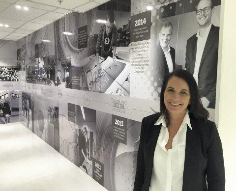 MED HISTORIEN I RYGGEN: Country Manager Cecilie Gaustad foran veggen             som viser historien til tradisjonsrike FotoKnudsen. Selskapet har gått gjennom både eierskifte og kraftige kutt i arbeidsstokken for å møte nye, digitale behov i markedet.FOTO: SVEIN TORE HAVRE