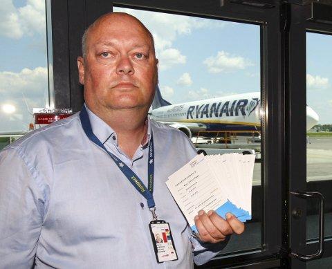 Krevende tid: Bunken med sommerparkeringsbevis som flystasjonssjef Kjell Espen Skjævestad her holder, er like stor som bunken med oppsigelser som han nå må sette seg ned å skrive. Alle Foto: Geir Hansen