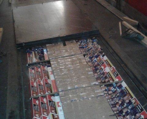 I GULVET: Tollerne fant store mengder sigaretter skrudd inn i gulvet på tilhengeren. Foto: Tolletaten