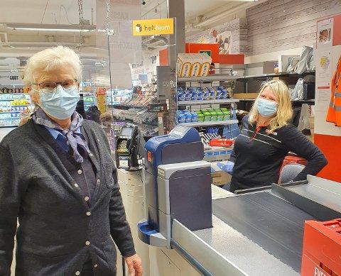 Trude Frøislihagen Dokken i kassa  smiler godt bak masken.  Sigrid Marie Hollerud har tatt seg turen fra polet ved siden av for å handle og gratulere. Foto:Rune Stenslette.