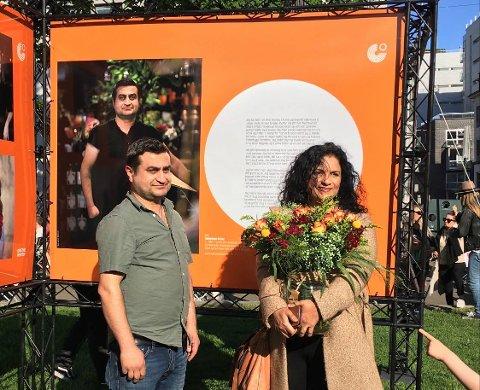 BLOMSTER: Fotograf Iffit Qureshi fikk blomster under åpningen. Suleyman Ortac er med i utstillingen og ser på bildet av seg selv.