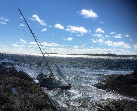 DREV I LAND: Denne seilbåten fikk problemer i den kraftige vinden fredag. Heldigvis greide kapteinen å komme seg i land. Foto: Bamble brannvesen