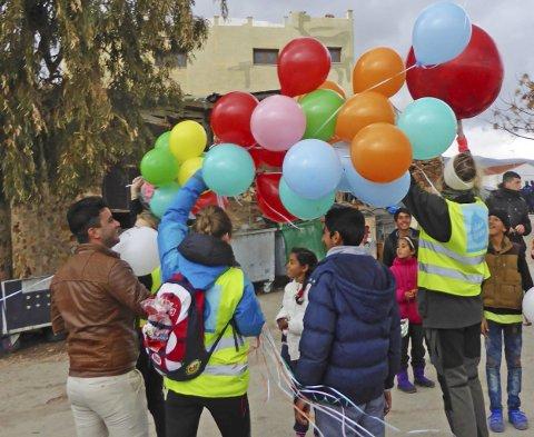 Barna lyser opp: Silje og ungdommene fra Norge deler ut ballonger til flyktningebarna. Foto: privat