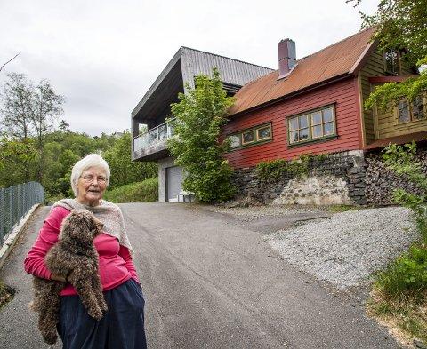 Synnøve Grønn er pensjonert lege, og bor sammen med hunden Fantus på Søreide. Det røde bygget er en gammel løe med både peisestue og matkjeller. FOTO: EIRIK HAGESÆTER