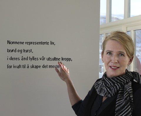 MALT PÅ VEGGEN: Kristin Solstad presenterer en versetekst som var malt på veggen til tilbygget De Tre Nonner.