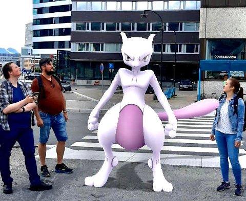 MIDTPUNKT: Deltakerne på Pokémon Go-Fest i Tromsø jakter animerte figurer ved hjelp av mobilen. Her har Niklas Jensvoll, Tor-Iver Sørensen og Miriam Nilsen fått selskap av selveste Mewtwo.