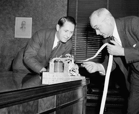 STORE KONSEKVENSER: Thomas Midgley Jr. (til høyre) ble av samtiden oppfattet som en anerkjent vitenskapsmann. I virkeligheten gjorde hans oppfinnelser ufattelig skade. Her er han avbildet i Washington i 1940 hvor han viser frem en morsemaskin til Conway P. Coe fra Patentstyret i USA.