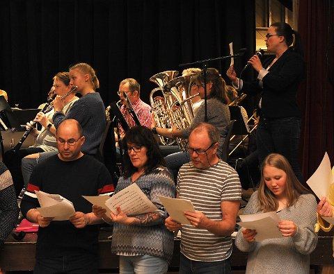 Konsentrerte sangere, solist og musikere på øvelse.