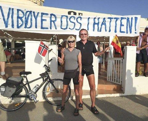 MOTTAKELSEN: Kari og Dag Langholm ble tatt i mot av landsmenn med flagg og plakat i La Manga etter to måneder på hjul gjennom Europa.