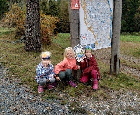 UT PÅ TUR: Agnes, Emilie og Ingeborg ved en av ti poster som er hengt opp.