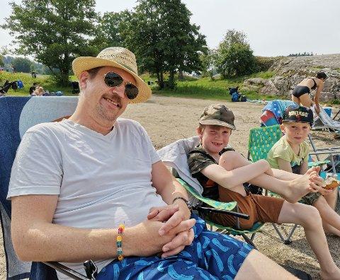 For Steffen Hempel (40), Edvin Hempel(7) og Alfred (3) er det best å sitte og nyte været før de kaster seg uti havet.
