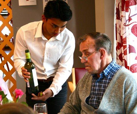 VIN TIL MATEN: Junie Lirjo (17) serverer Magnus Bråthen (88) i restauranten på Jors.