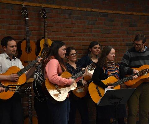 Stiller opp: Her stiller koret seg opp med gitarer for en video korarrangøren vil lage.