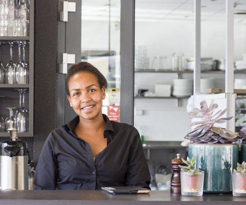 – FORTJENER DET: Servitør ved Sjøbris restaurant og bar, Kamilla McCullough, sier at de ble kjempeglade for smilefjeset. – Vi fortjener det også, mener hun. Foto: Kristine Aas