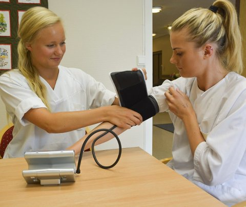 Blodtrykk: Noen av arbeidsoppgavene til Line og Anette er å måle blodtrykket til pasientene. Her øver de på hverandre.