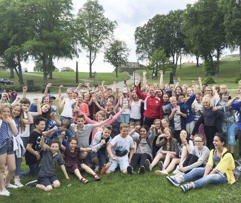 BLØT JUBEL: Frøydis Aarum (i midten med rød HK Halden genser) er lærer ved Folkvang skole. Et tapt «veddemål» med elevene gjorde at hun måtte bade i andedammen på festningen – med elevene i 5.- 6.- og 7. trinn som fornøyde tilskuere.Foto: Privat