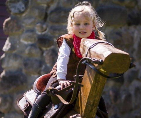 RIR PÅ TREHEST: To år gamle Lilli Elena Mellingen Grønnli koste seg på trehestane. Men å kasta hestesko var enno kjekkare. – Hivet på den stangen, så klara eg det. Det var kjekt, seier ho strålande nøgd.