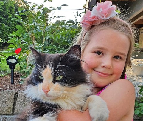 ORANSJE:  Mariannes datter med katten Elsa (4) , som stadig kommer hjem med oransjefarget snute og pels.