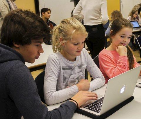 Koding: Trym Ramberg (16) gjør Sofie Grimsgaar (9) og Milla Nicoline Nygård Dalen (9) kjent med koding. foto: h. Slaatsveen