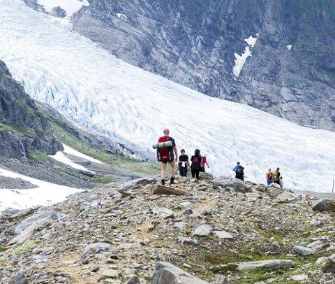 Her er en gruppe på vei ned stien fra Tåkeheimen, med panoramautsikt til bretunga Engenbreen eller Engabreen.